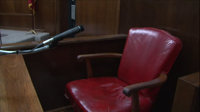 a microphone faces a red chair on a courtroom witness stand. - palazzo di giustizia video stock e b–roll