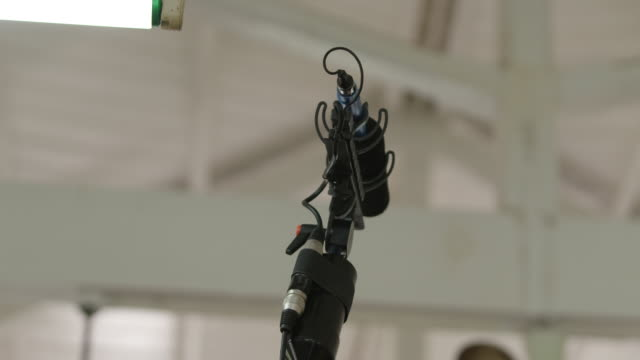 microphone on a boom pole in a room painted white - microphone stock videos & royalty-free footage