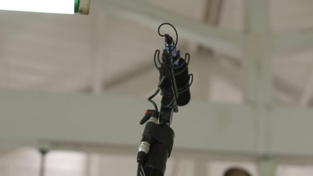 microphone on a boom pole in a room painted white - mikrofon bildbanksvideor och videomaterial från bakom kulisserna
