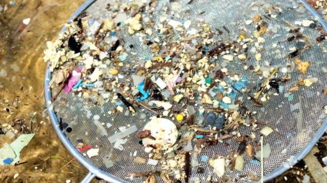 vídeos de stock, filmes e b-roll de microplásticos são pedaços muito pequenos de plástico que poluem o meio ambiente. - poluição do plástico