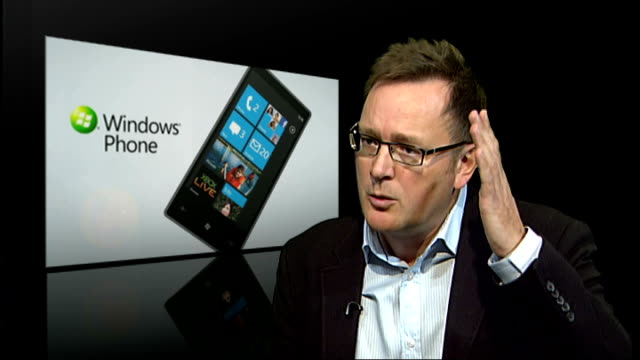 Microsoft launches Windows Phone 7 ** BEWARE Man leaving shop holding up new Windows 7 smartphone as people stand and applaud Man with Windows 7...
