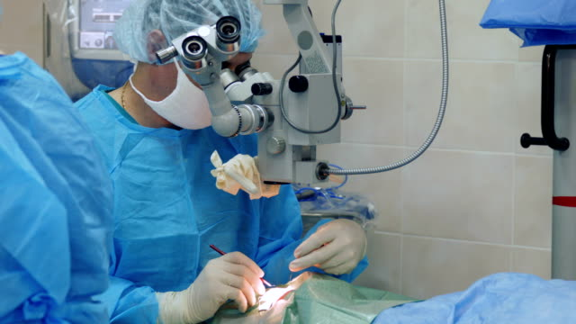 micro-surgeon working at operating room - lens optical instrument stock videos & royalty-free footage