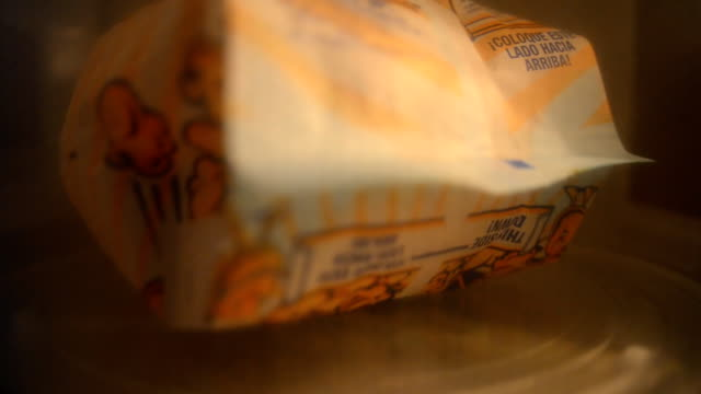 vídeos de stock, filmes e b-roll de preparação de pipoca de micro-ondas - pipoca