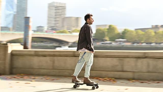 vídeos de stock e filmes b-roll de mid 30s male commuter skateboarding along thames embankment - perto