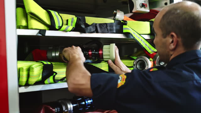 mid 30s male first responder securing hoses on fire engine - fire station stock videos & royalty-free footage