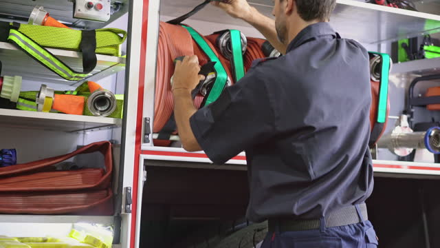 mid 40s firefighter checking equipment on emergency vehicle - fire station stock videos & royalty-free footage