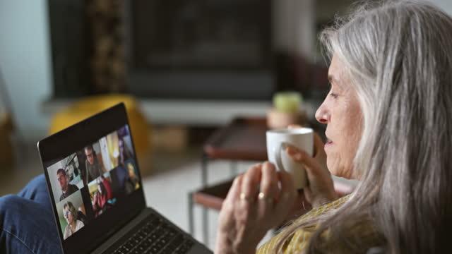週末のビデオ通話で友人に追いつく60年代半ばの女性 - individuality点の映像素材/bロール