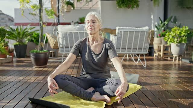vidéos et rushes de femme du milieu des années 60 faisant le yoga à l'extérieur sur le pont ensoleillé - yeux fermés