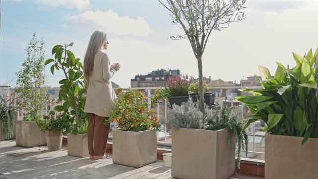 vídeos de stock, filmes e b-roll de mulher dos anos 60 curtindo café e barcelona vista em casa - pátio