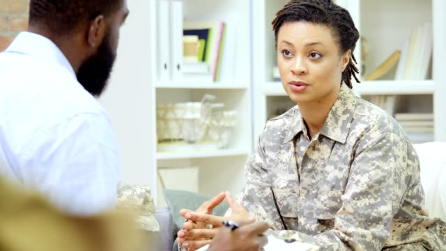mid adult african american female veteran discusses issues with mental health professional - terapia alternativa video stock e b–roll