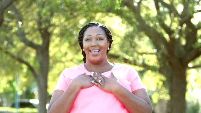 mid adult african-american woman standing in park - corporatura larga video stock e b–roll
