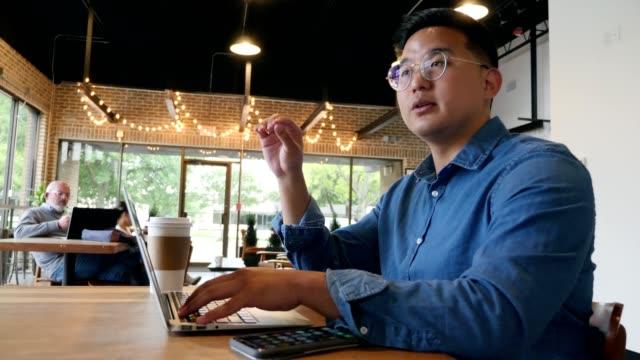 ミッドアダルトアジアのビジネスマンは、コーヒーショップでクライアントと会う - ビジネスカジュアル点の映像素材/bロール