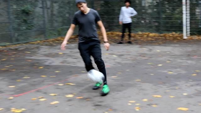 mid adult athlete taking penalty kick on street - hitting stock videos & royalty-free footage