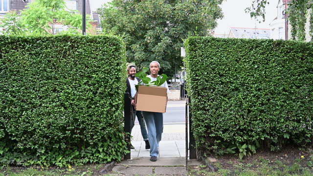 mid adult black couple carrying box and chairs on moving day - 35 39 years stock videos & royalty-free footage