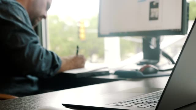 vidéos et rushes de l'homme d'affaires adulte moyen prend des notes dans le cahier tout en faisant des plans pour un projet - carnet