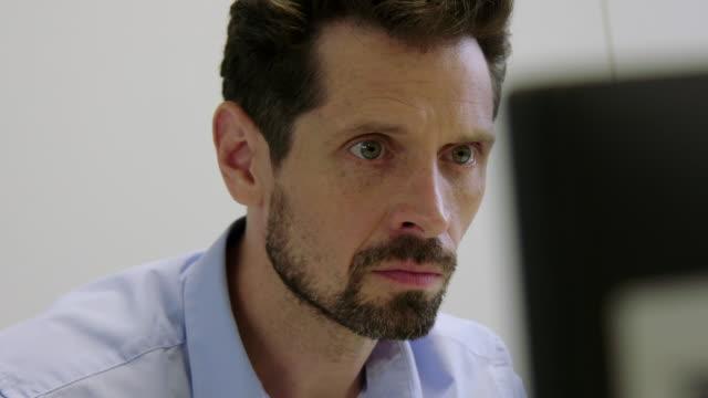 mittlere randalierte geschäftsmann arbeitet an seinem schreibtisch und lächelnd - e mail stock-videos und b-roll-filmmaterial