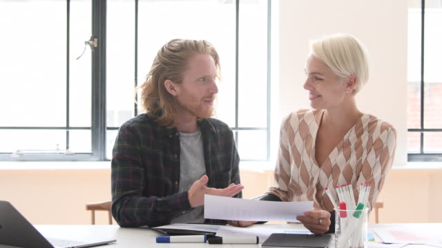 mid adult businesswoman talking to young man with long red hair in office - long hair stock videos & royalty-free footage