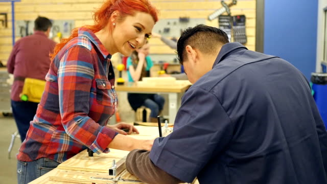 Mid adult Caucasian woman and Hispanic man work on woodworking project in community workshop
