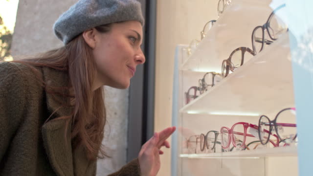 mid adult caucasian woman looking for eyeglasses at window store - occhiali da vista video stock e b–roll