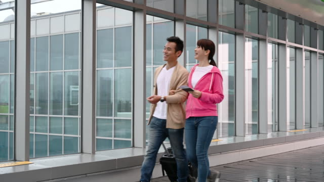 mid adult chinese couple walking to airport gate - mid adult couple stock videos & royalty-free footage
