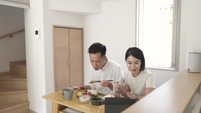 mid adult couple and friends connecting together on video calls at lunchtime. - mid adult couple stock videos & royalty-free footage