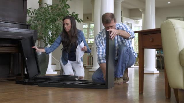 mid adult couple assembling a low shelving unit - heimwerken stock-videos und b-roll-filmmaterial