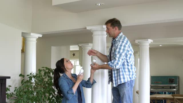 mid adult couple changing a light bulb - energy efficient lightbulb stock videos & royalty-free footage