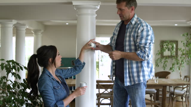 Mid adult couple changing a light bulb