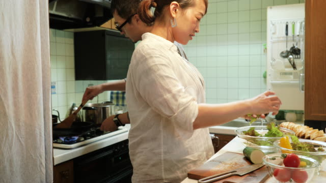 Mid adult couple cooking at kitchen
