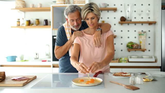 vídeos de stock e filmes b-roll de mid adult couple cooking breakfast together. - 60 64 anos