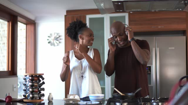 mid adult couple dancing and having fun while cooking at home - mid adult couple stock videos & royalty-free footage