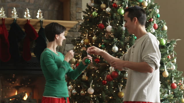 mid adult couple decorating a christmas tree with ornaments - mid adult couple stock videos & royalty-free footage