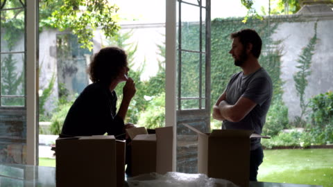mid adult couple discussing by window at new home - mid adult couple stock videos & royalty-free footage