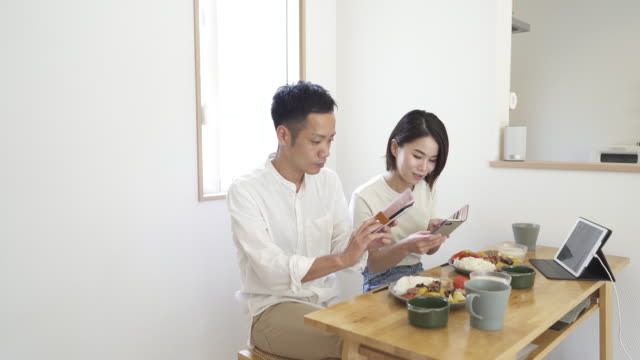 mid adult couple eating lunch together in the living room of home. - mid adult couple stock videos & royalty-free footage