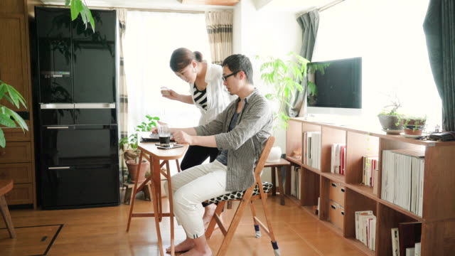 半ば楽しんでいる大人のカップルが家庭で話す - 家の中点の映像素材/bロール
