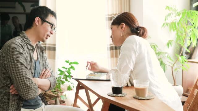 半ば楽しんでいる大人のカップルが家庭で話す