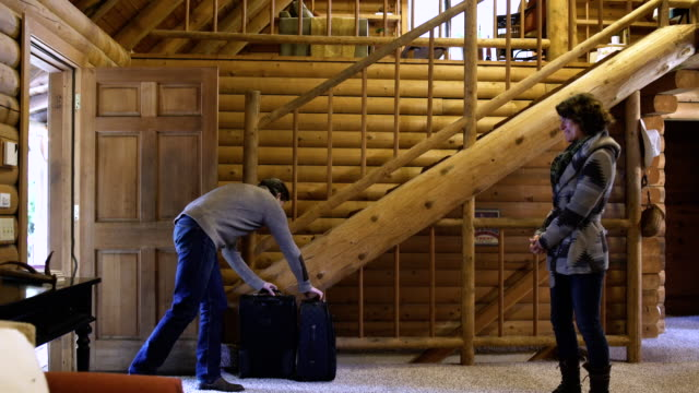 Mid adult couple entering a log cabin