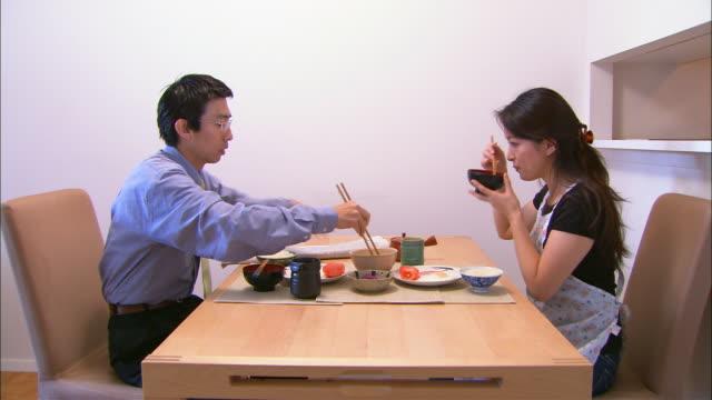 ms, mid adult couple having washoku style breakfast - 対面点の映像素材/bロール