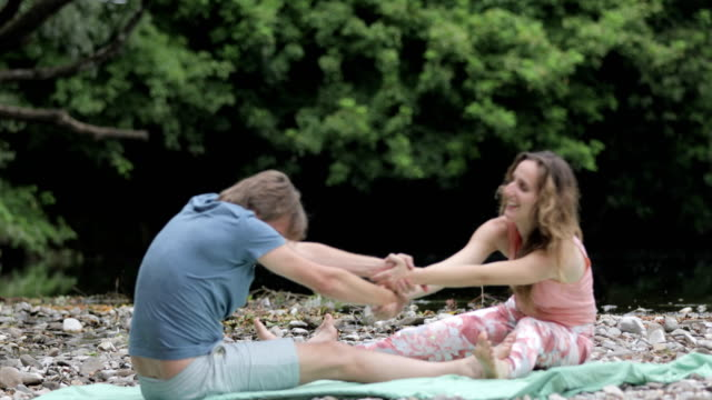 mid adult couple holding hands and doing yoga exercise - mid adult couple stock videos & royalty-free footage