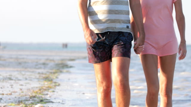 mid adult couple holding hands and walking on coastline - mid adult couple stock videos & royalty-free footage
