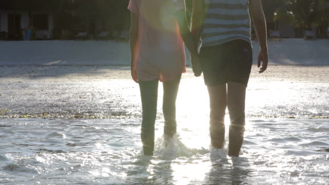 Mid Adult Couple Holding Hands and Walking Out of the Sea