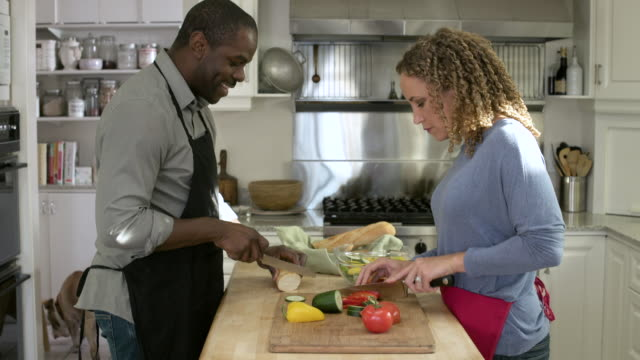 Mid adult couple looking at camera while preparing meal