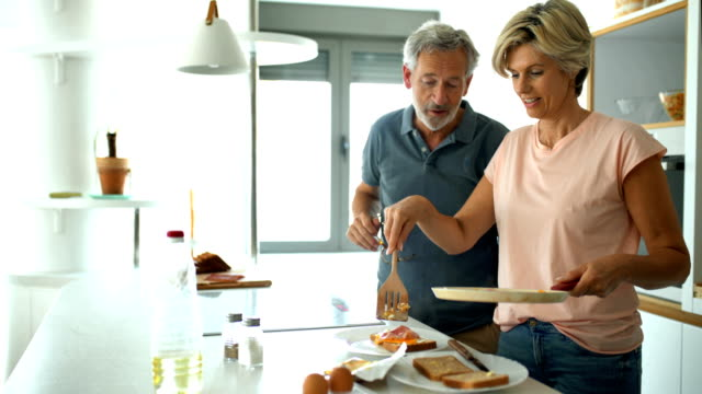 mid adult couple making breakfast together. - mature couple stock videos & royalty-free footage