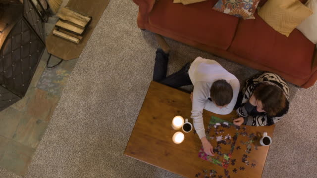 stockvideo's en b-roll-footage met mid adult couple playing puzzle - puzzel