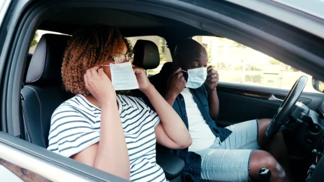 mid adult couple putting on protective face masks in car - prevenzione delle malattie video stock e b–roll