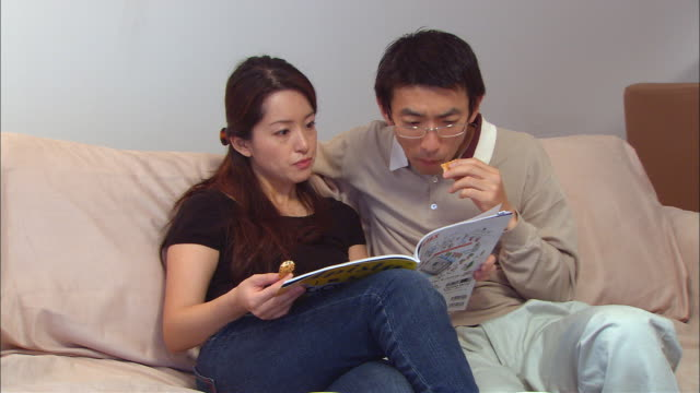 ms, mid adult couple reading magazine and eating senbei crackers - 雑誌点の映像素材/bロール
