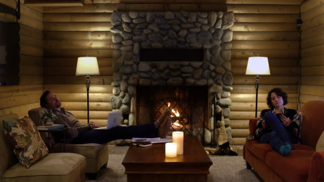 mid adult couple resting in a log cabin - stone material stock videos & royalty-free footage