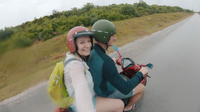 pov mid adult couple riding a scooter on a country road in tanzania - motorbike stock videos & royalty-free footage