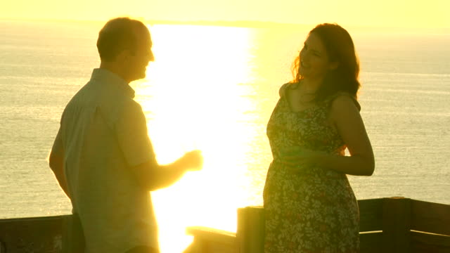 ms, mid adult couple standing by railing, overlooking ocean and drinking, sunset, north truro, massachusetts, usa - mid adult couple stock videos & royalty-free footage