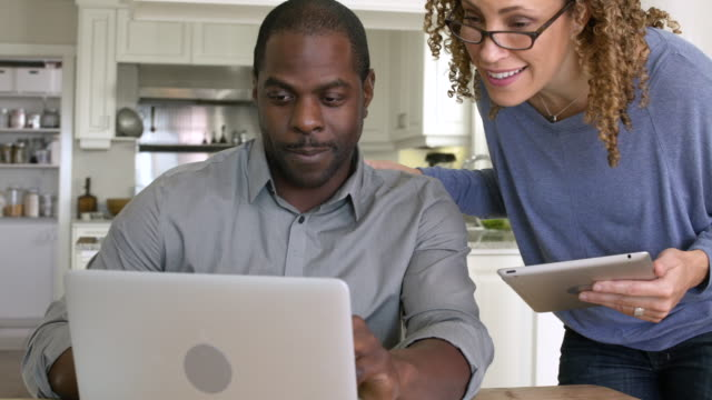 Mid adult couple talking over a laptop